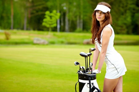 woman golf: Portrait of an elegant woman playing golf on a green woman