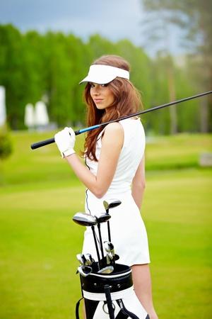 club dress: Portrait of an elegant woman playing golf on a green woman