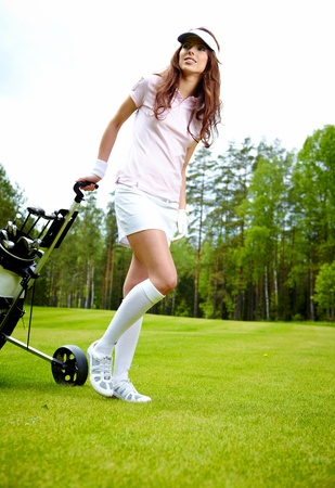 female golf player walking on fairway with their golf trolleys photo