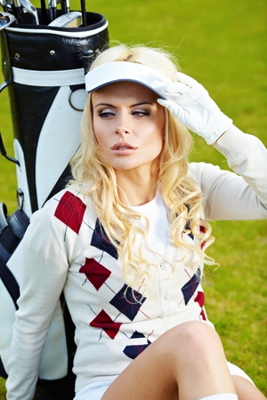 A beautiful blond haired blue eyed young woman playing golf  photo