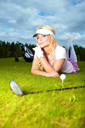 Woman placing a golf ball on the course  photo