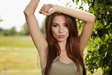 1 adult only: Young woman outdoors portrait. Soft sunny colors.