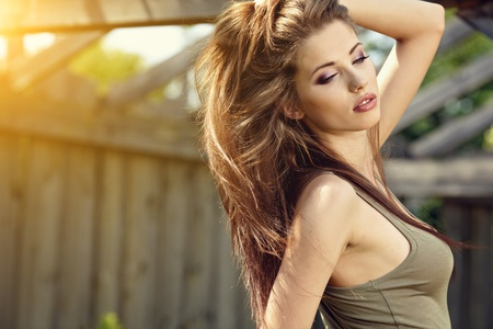 adults only: Young woman outdoors portrait. Soft sunny colors.