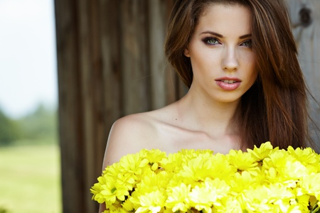 Closeup portrait of cute young girl with yellow flowers smiling outdoors  Stock Photo - 9765718