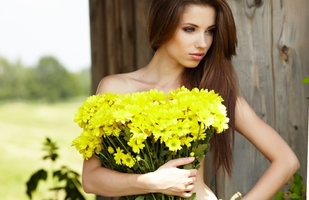Closeup portrait of cute young girl with yellow flowers smiling outdoors Stock Photo - 9765709