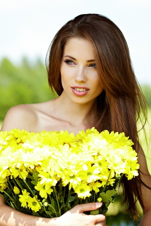 Closeup portrait of cute young girl with yellow flowers smiling outdoors Stock Photo - 9763485