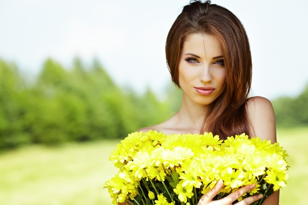 Closeup portrait of cute young girl with yellow flowers smiling outdoors  Stock Photo - 9765715
