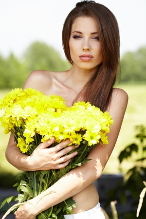 Closeup portrait of cute young girl with yellow flowers smiling outdoors Stock Photo - 9763570