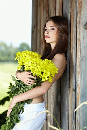 Closeup portrait of cute young girl with yellow flowers smiling outdoors Stock Photo - 9763033