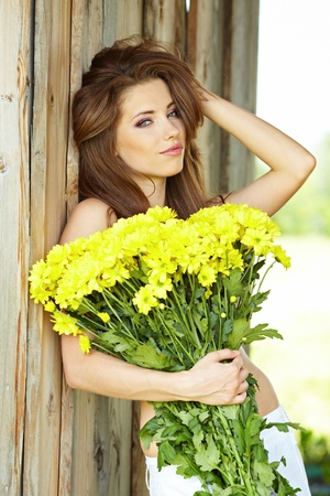 Closeup portrait of cute young girl with yellow flowers smiling outdoors Stock Photo - 9763037