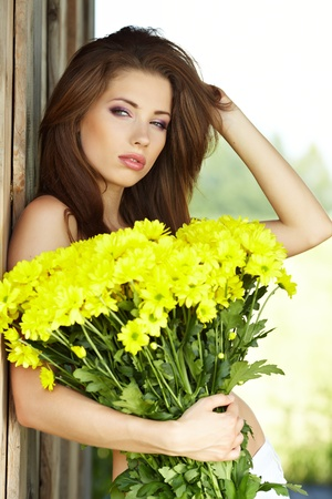 Closeup portrait of cute young girl with yellow flowers smiling outdoors Stock Photo - 9763569