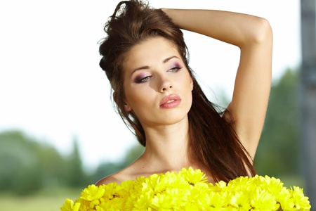 Closeup portrait of cute young girl with yellow flowers smiling outdoors  Stock Photo - 9765705
