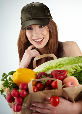 Portrait of happy woman holding a shopping bag full of groceries on white background  photo