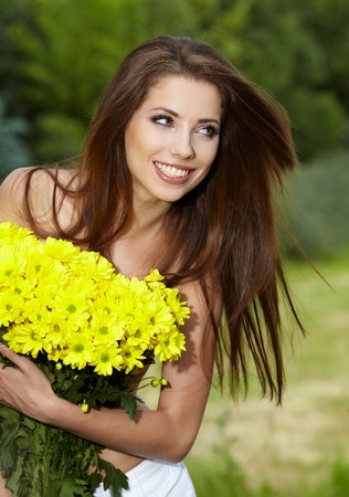 Young woman holding yellow flowers photo