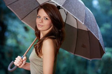 woman umbrella: Beautiful woman holding umbrella out in the rain