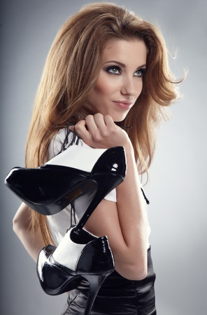young feet: Beautiful woman after party holding shoes . Girl and shoe  Stock Photo