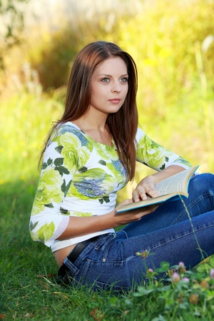 barefooted: Young  woman studying in summer park