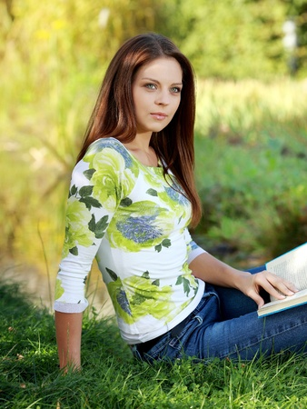 Young  woman studying in summer park photo