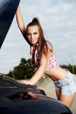 damaged: beautiful young woman repairing the car  Stock Photo