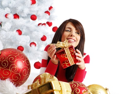 smile christmas decorations: young woman with gift box next to white christmas tree