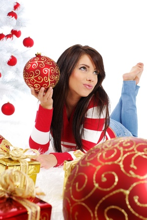 young woman with gift box next to white christmas tree photo