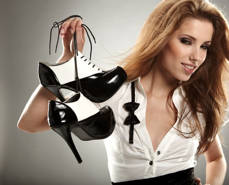 after the party: Beautiful woman after party holding shoes . Girl and shoe  Stock Photo