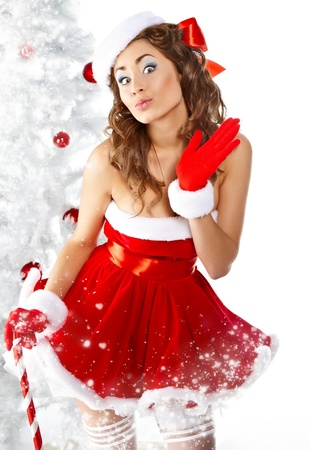 Beautiful young woman in Santa Claus clothes holding presents over Christmas background.  Stock Photo - 10931338