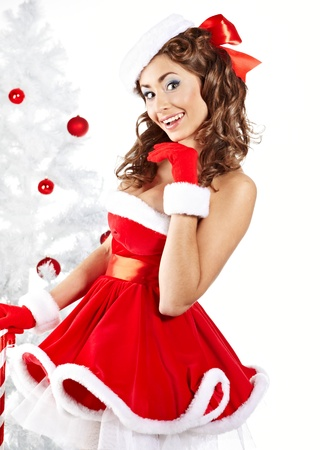 Beautiful young woman in Santa Claus clothes holding presents over Christmas background.  photo