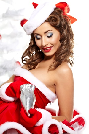 Beautiful young woman in Santa Claus clothes holding presents over Christmas background. Stock Photo - 10931340