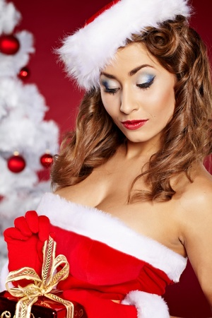 20-25 years olf beautiful woman next to christmas tree on red background  photo