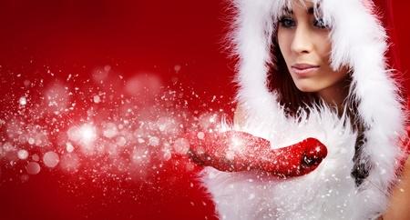 Retrato de hermosa chica sexy vistiendo ropas de santa claus en fondo rojo