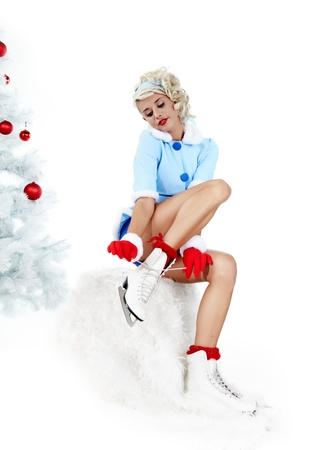 Pinup woman in winter style with skates. Isolated on white background  photo