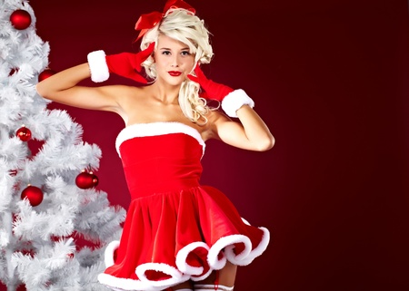 Happy cute girl in santa claus suit over red background Stock Photo - 10982358