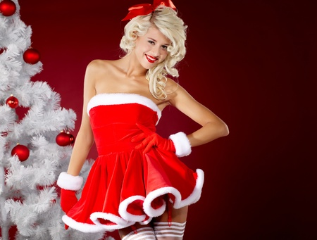Happy cute girl in santa claus suit over red background Stock Photo - 10982354