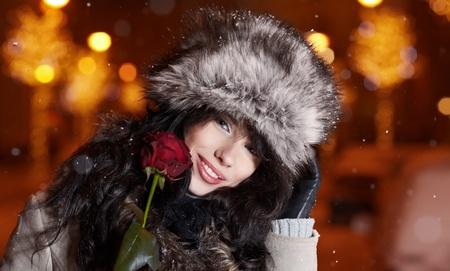 Woman in night city holding red rose. Valentine photo