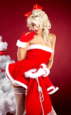 Happy cute girl in santa claus suit over red background  photo