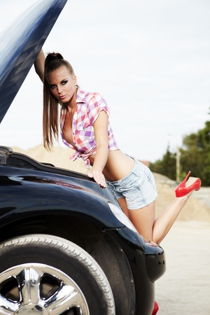 young sexy woman with her broken car. photo