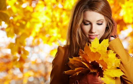 Young woman with autumn leaves in hand and fall yellow maple garden background  photo