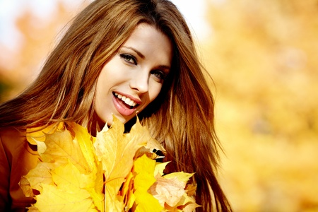 russian girls: Young woman with autumn leaves in hand and fall yellow maple garden background