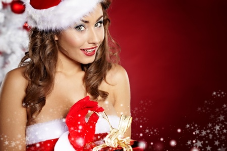 christmas girl: sexy girl smiles and holding a gift in magic packing  Stock Photo