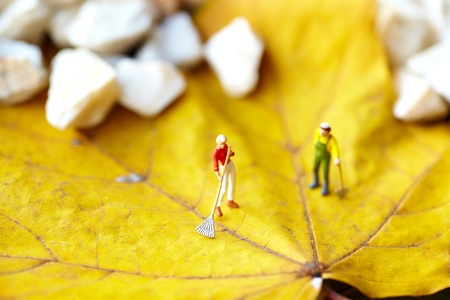 Miniature figurine  using a rake to clean up of the fallen leaves  photo