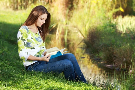 sun down: Attractive girl student reading book in autumn park.