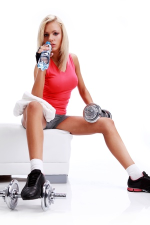 seated: Sporty female sitting in the gym with bottle of water in hands Stock Photo