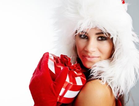 Christmas gifts. Woman wrapping christmas presents wearing santa hat. Stock Photo - 11292413
