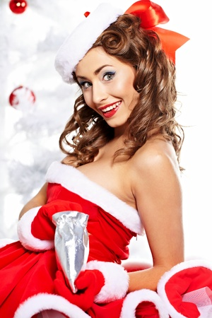 make a gift: Fashionable young woman in Santa Claus clothes with presents
