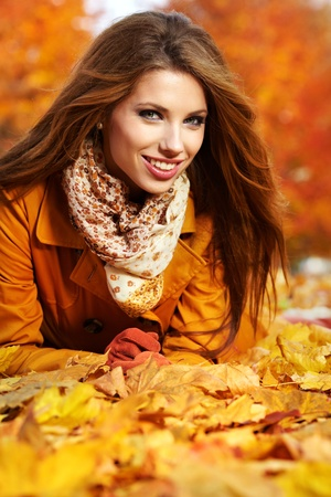 Portrait of an autumn woman lying over leaves and smiling  photo