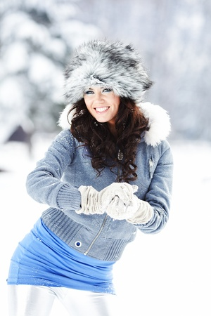 Happy young  woman plays with a snow photo