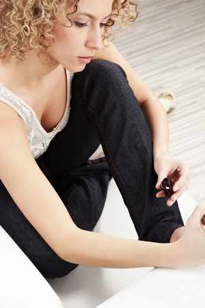 Beautiful Woman applying nail polish Stock Photo