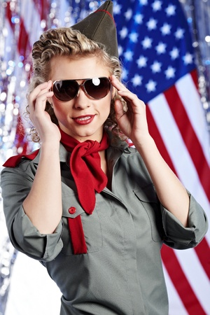camos: Pin-up army woman  standing near the American flag