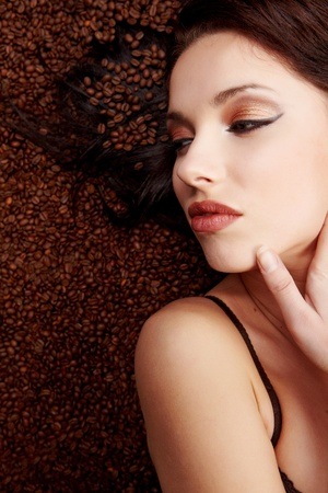 portrait of beautiful young woman with coffee beans around her photo
